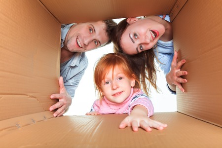 family moving house: The smiling family in a cardboard box ready for moving house