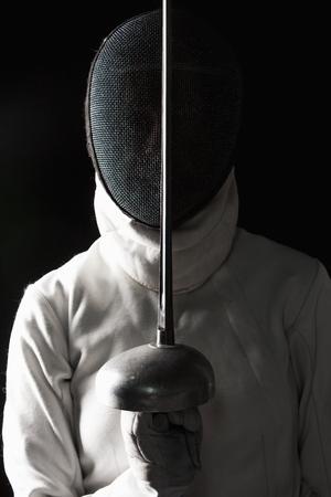 Het portret van de vrouw, gekleed in witte schermen kostuum en zwarte schermen masker met de rapier op zwarte achtergrond