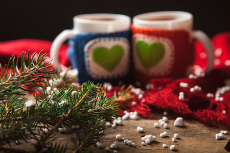 warm things: Two warm cups of tea or coffee with red and blue knitted thing on it and with heart for Valentines day