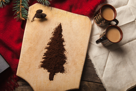 christmas ground: The two cups of coffee on wooden background and christmas tree made of ground coffee on a cutting board