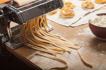 throe: The pasta and pasta machine on wooden kitchen table Stock Photo