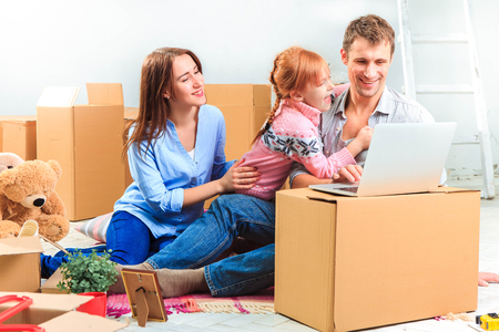 house moving: The happy family with laptop at repair and relocation on a background of boxes