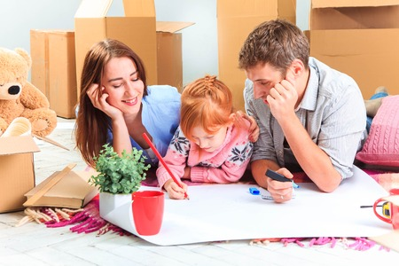 house moving: The happy family  at repair and relocation. The family planing  to accommodation on a background of boxes