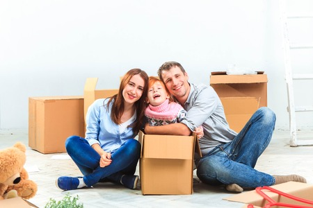 unpacking: The happy family  at repair and relocation on a background of boxes