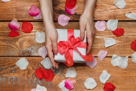 love shape: Valentines Day gift in white box and Female hands and petals on wooden background