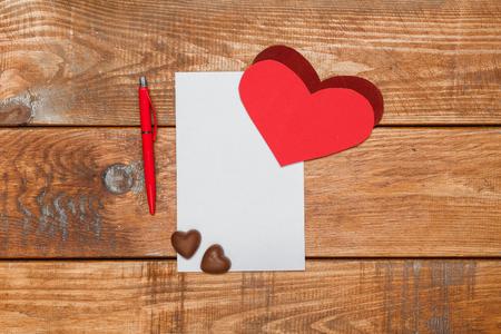 hoja en blanco: La cinta roja, pequeños corazones y hoja de papel y lápiz sobre fondo de madera