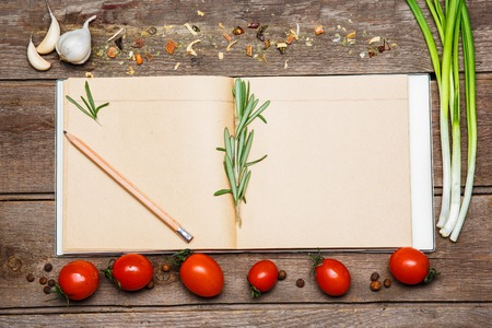 recipe background: Open blank recipe book on brown wooden background with tomatoes, garlic,  green onion