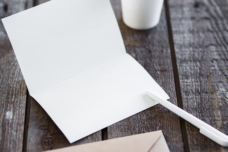 boligrafos: En blanco tarjeta de saludos de invitación para reemplazar su diseño en la mesa de madera de color gris