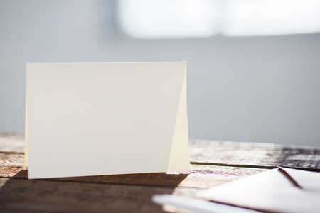 replace: Blank invitation greetings card to replace your design on gray wooden table Stock Photo