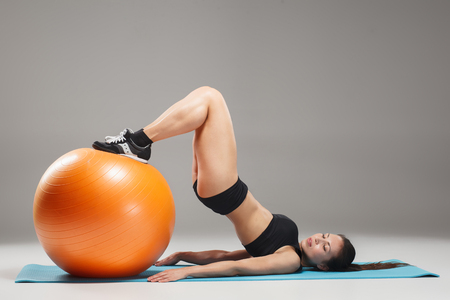 fitball: The young, beautiful, sports girl doing exercises on a fitball at the gym on gray background