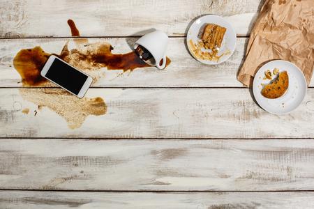 Kopje koffie gemorst op houten tafel met de telefoon en de resten van een maaltijd