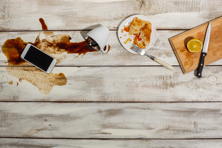 remnants: Cup of coffee spilled on wooden table with the phone and and the remnants of a meal