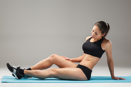 bracing: The  muscular young woman athlete stretching on gray background. Stock Photo