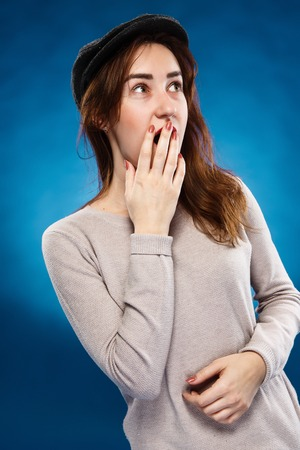mouthed: Close-up portrait of surprised beautiful girl in cap holding her head in amazement and open-mouthed over blue background. Stock Photo