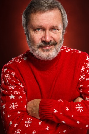 kindly: Elderly smiling  kindly man in red sweater on a red  background
