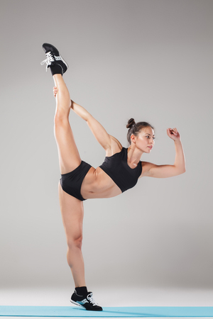 asana: Beautiful sporty girl standing in acrobat pose or yoga asana on gray background Stock Photo