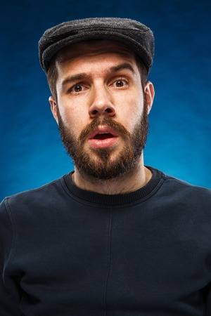 The portrait of a young beautiful man in cap with surprised face expression on blue background Stock Photo