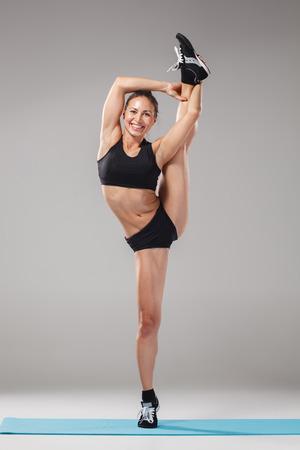 acrobat: Beautiful sporty girl standing in acrobat pose or yoga asana on gray background Stock Photo