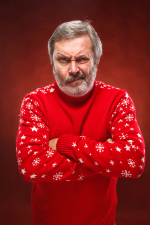 exasperation: The expressive portrait on red background of a pouter unhappy older man in a red sweater Stock Photo