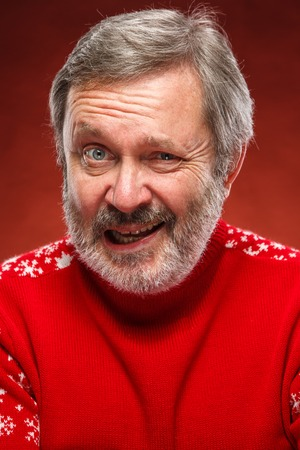 grumpy old man: The expressive portrait on red background of a pouter unhappy older man in a red sweater. The concept of evil smile Stock Photo