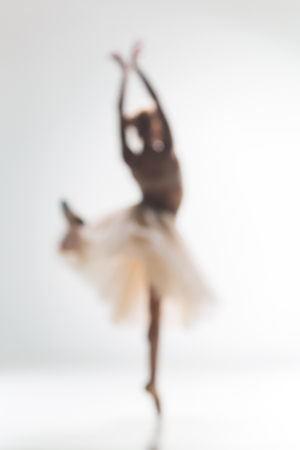 pirouette: Blurred silhouette of ballerina dancing on white background