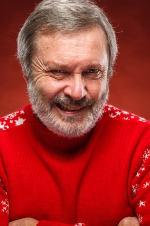 exasperation: The expressive portrait on red background of a pouter unhappy older man in a red sweater. The concept of evil smile Stock Photo