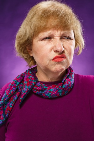 The portrait of a disaffected senior woman on lilac background