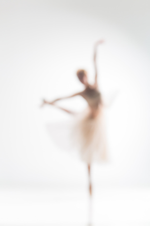 Blurred silhouette of ballerina dancing on white background
