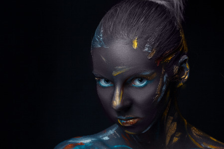 airbrushing: Portrait of a young woman who is posing covered with black paint in the studio on a black background Stock Photo