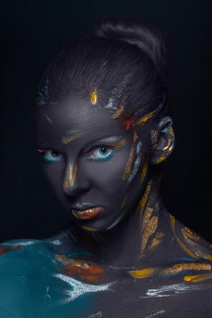 Portrait einer jungen Frau, die mit schwarzer Farbe im Studio auf einem schwarzen Hintergrund bedeckt ist Aufstellung