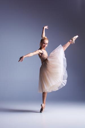 De jonge mooie moderne stijl danser die zich voordeed op een studio grijze achtergrond