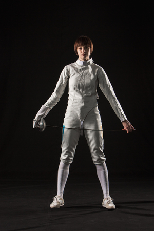 rapier: The portrait of woman wearing white fencing costume and black fencing mask  with the rapier on black background