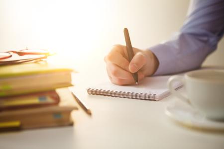 hombre escribiendo: La mano masculina con una pluma y la taza de caf� y de cuaderno