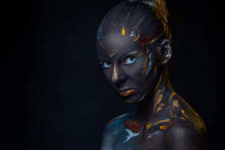 expresion corporal: Retrato de una mujer joven que est� presentando cubierta con pintura negro en el estudio sobre un fondo negro