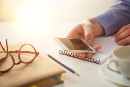 empresarial: La mano masculina que sostiene un teléfono contra el fondo de la tabla