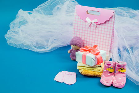 The baby clothes with a white gift box on blue background