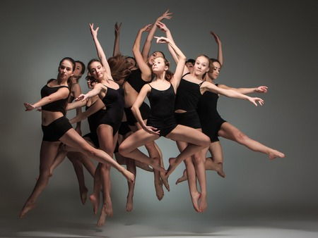 contemporary dance: The group of modern ballet dancers jumping on gray background Stock Photo