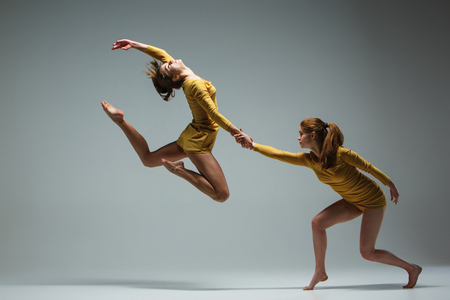 The two modern ballet dancers dancing on gray background Stock Photo