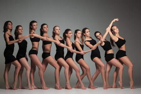 The group of modern ballet dancers posing on gray background