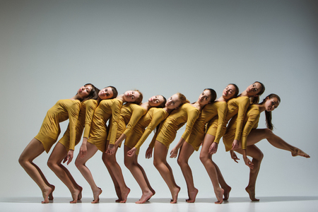 action girl: The group of modern ballet dancers dancing on gray background