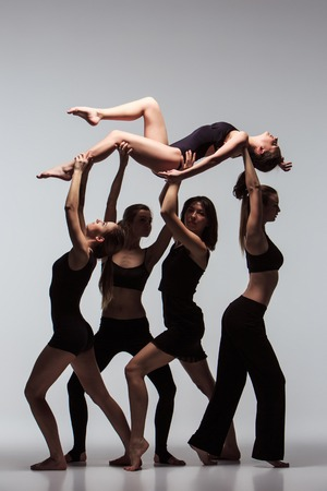 The group of modern ballet dancers posing on gray background. Фото со стока