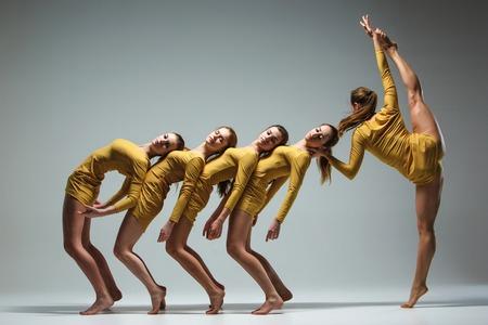 Die Gruppe der modernen Ballett-Tänzer auf grauem Hintergrund tanzen