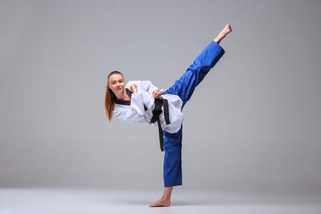 La jeune fille de karaté en kimono blanc et ceinture noire de karaté de formation sur fond gris.