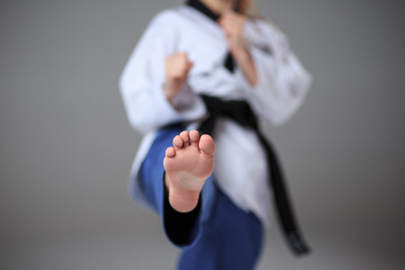 girl punch: The foot of karate girl in white kimono and black belt training karate over gray background.
