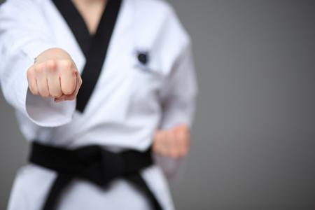 karateka: The hand of karate girl in white kimono and black belt training karate over gray background.