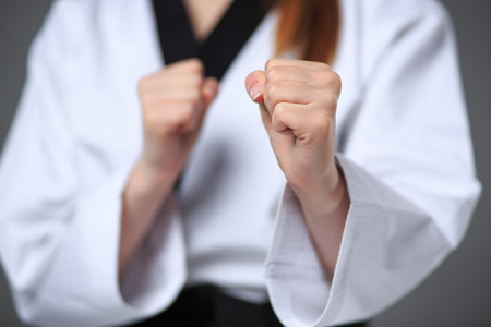 girl punch: The hands of karate girl in white kimono and black belt training karate over gray background.