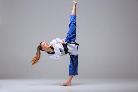 La muchacha del karate en el kimono blanco y negro de karate de entrenamiento cinta sobre fondo gris.