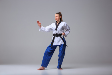 karateka: The karate girl in white kimono and black belt training karate over gray background.