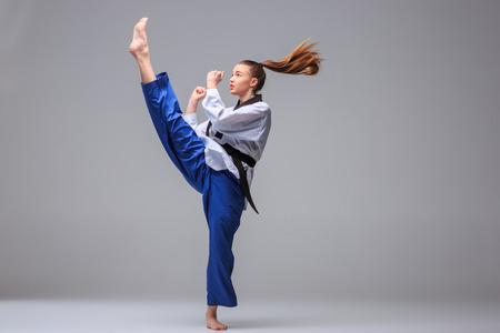Das Karate Mädchen im weißen Kimono und schwarzen Gürtel Karate Training auf grauem Hintergrund.