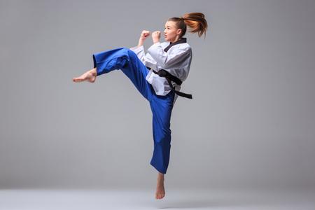 patada: La muchacha del karate en el kimono blanco y negro de karate de entrenamiento cinta sobre fondo gris.